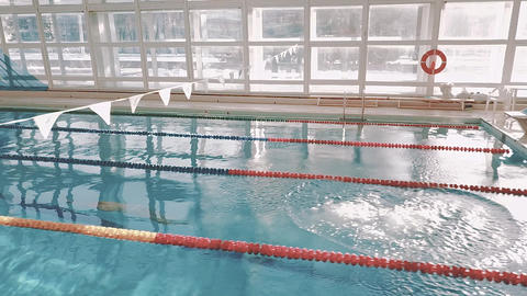 Jump into the water in the pool. The swimmer dives and swims under the water Footage