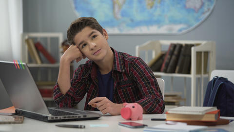 Teen dreaming of new gadget, collecting money in piggy bank, financial literacy Live Action