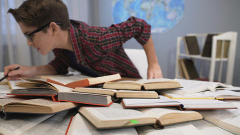 Boy enthusiastically with interest searching for information in pile of books ライブ動画