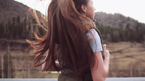 A beautiful girl with long hair runs along a mountain road. Slow motion. Hair Footage
