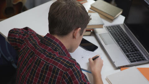 Child reluctantly doing homework under close attention of strict parents Footage