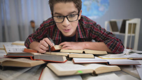 Boy carefully and attentively studying literature, huge pile of books on table Footage
