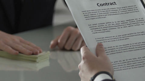 Corporate manager signing paper agreement with cash on table, investment deal Footage