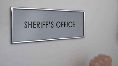Sheriff office door, hand knocking, law enforcement officer, crime prevention Footage