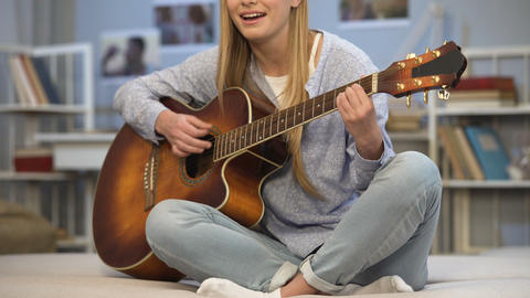 Talented inspired girl playing music instrument at friends party, entertainment Footage