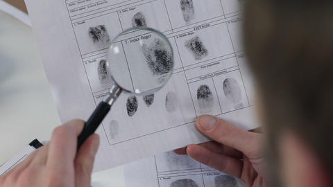 Police officer checking fingerprints file with magnifying glass, identification Live Action