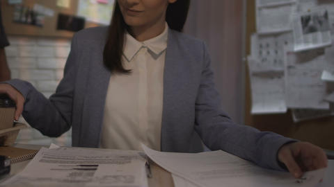 Lady reading files and drinking coffee offered by colleague, flirt on workplace Live Action