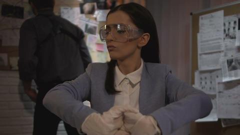 Lady criminalist in gloves holding bullet evidence in plastic bag, expertise Live Action