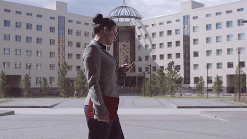 A beautiful business lady walks in the city and reads an email on the smartphone Footage