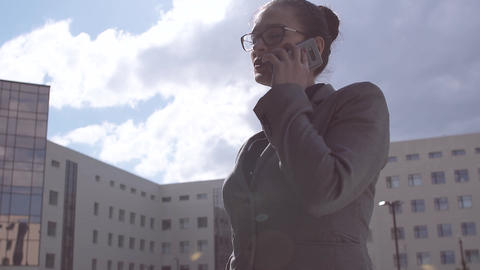 Beautiful business woman wearing glasses is talking on the phone on a cloudy sky Footage