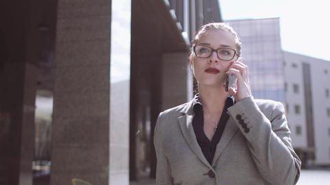 A beautiful girl with glasses goes and talks on the phone. The sun shines Footage