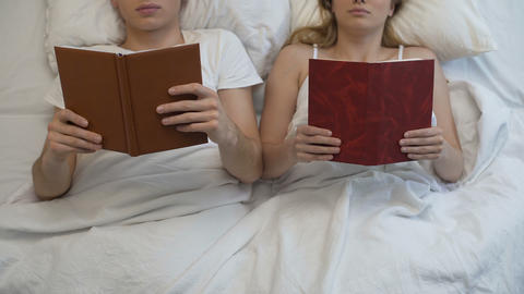 Young couple reading books in bed ignoring each other, intimate problem, rest Footage