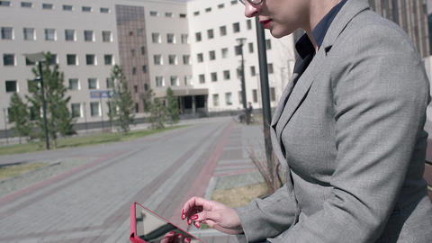 Businesswoman using tablet in the park in high quality format Footage