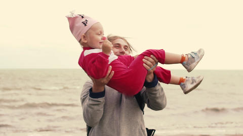 Funny father turns her daughter in her arms. On the sea shore Footage