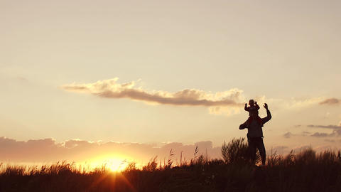 Father and daughter at sunset. Waving their hands. Slow motion Footage