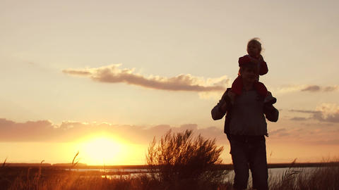Daughter on your dad's shoulders. Silhouettes at sunset Footage