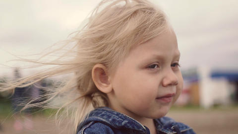 Blonde little girl smiling. Close-up. Hair fluttering in the wind Footage