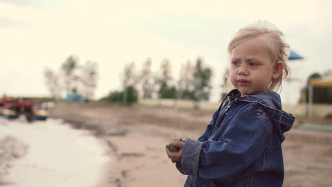 The little blonde girl throws sand in the sea ビデオ