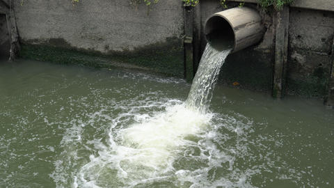 Water flows down from sewer into polluted pond in city Footage