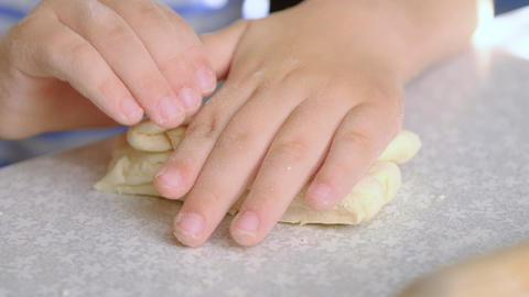 Children's rolling pin for dough. The child kneads the dough with his hands Footage