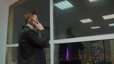 Successful business man calling to mobile phone on evening window background Footage