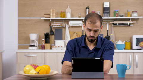 Man in the kitchen looking at digital tablet PC Live Action