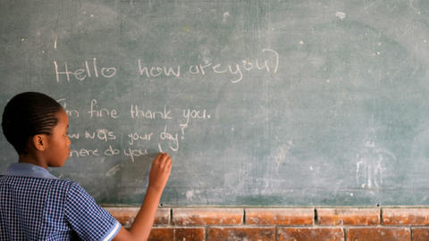 Schoolgirl writing on chalkboard in classroom 4k Live Action