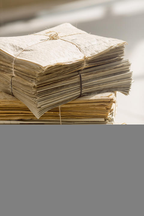Stack of old newspapers フォト
