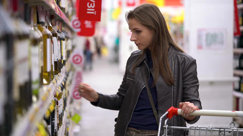 Woman chooses bottle of wine in the supermarket Live Action