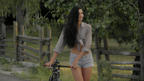 Young woman walking with a bicycle outdoor Archivo