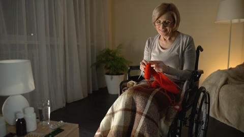 Cheerful old woman sitting in wheelchair knitting scarf, taking care of children Live Action