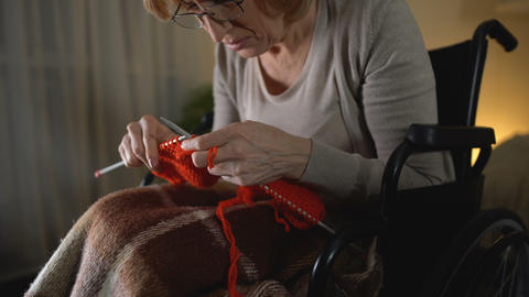 Old knitting woman feeling desperate of shaking hands illness, hopelessness Footage