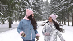 Two girlfriends run through the winter forest in a good mood Footage