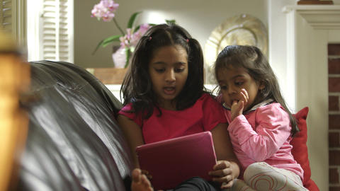 Older sibling sings along with what she and little sister see on tablet pc Footage