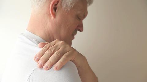 Man rubs and flexes his sore shoulder Footage