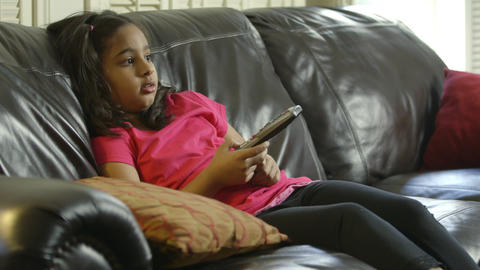 Young girl sitting on sofa changing TV channels using remote controller Footage