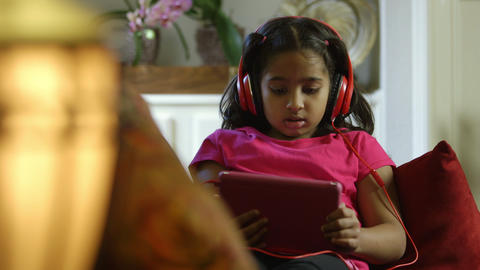 cute Indian child with headphones captivated by what is on her tablet pc Footage