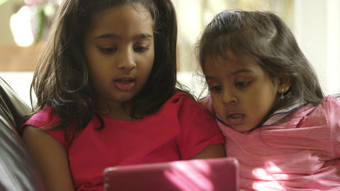 closeup of two cute little girls looking at a tablet pc Footage