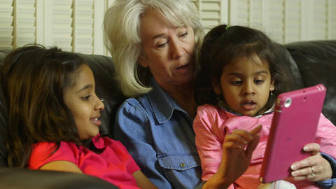 Children showing grandmother something on the tablet pc Live Action