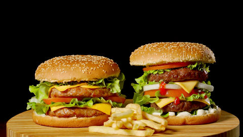 Two craft beef burgers on wooden table isolated on dark grayscale background Footage