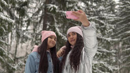 Two young girlfriends make selfie on the background of the winter forest using a Footage