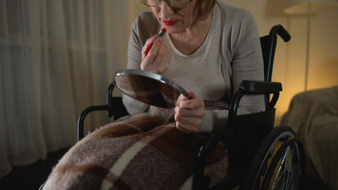 Upset old woman in wheelchair doing makeup, sighs with regret about youthfulness Live Action