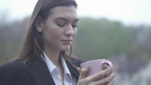 Pretty woman drinks hot coffee outdoors Girl drinking from a cup Portrait of a Footage