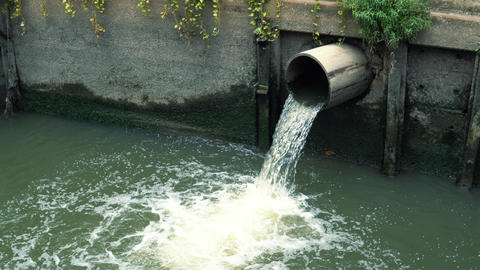 Drain polluted water through sewage into the canal at city street, side view ビデオ