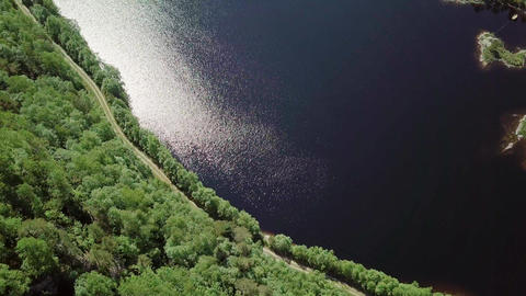 Small gravel road at shore of a lake, aerial shot ビデオ