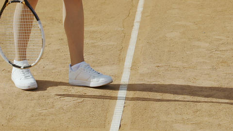 Woman serves tennis ball, comfortable shoes for active sports, legs close up Footage