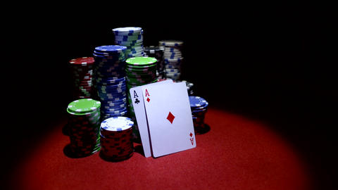 Pair of aces and poker chips on red table Footage