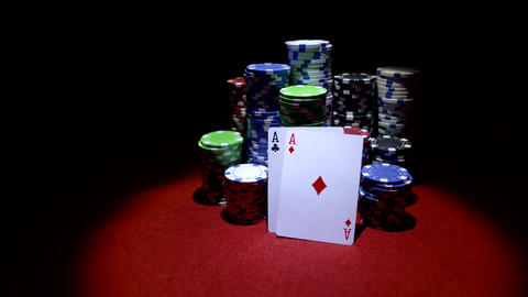 Pair of aces and poker chips on red table Stock Video Footage