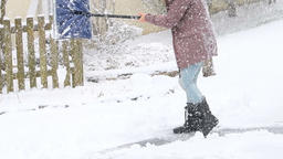 Slow motion of woman cleaning street, road from snow in winter, snowing Footage