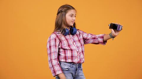 Young girl vlogging with a small camera Live Action